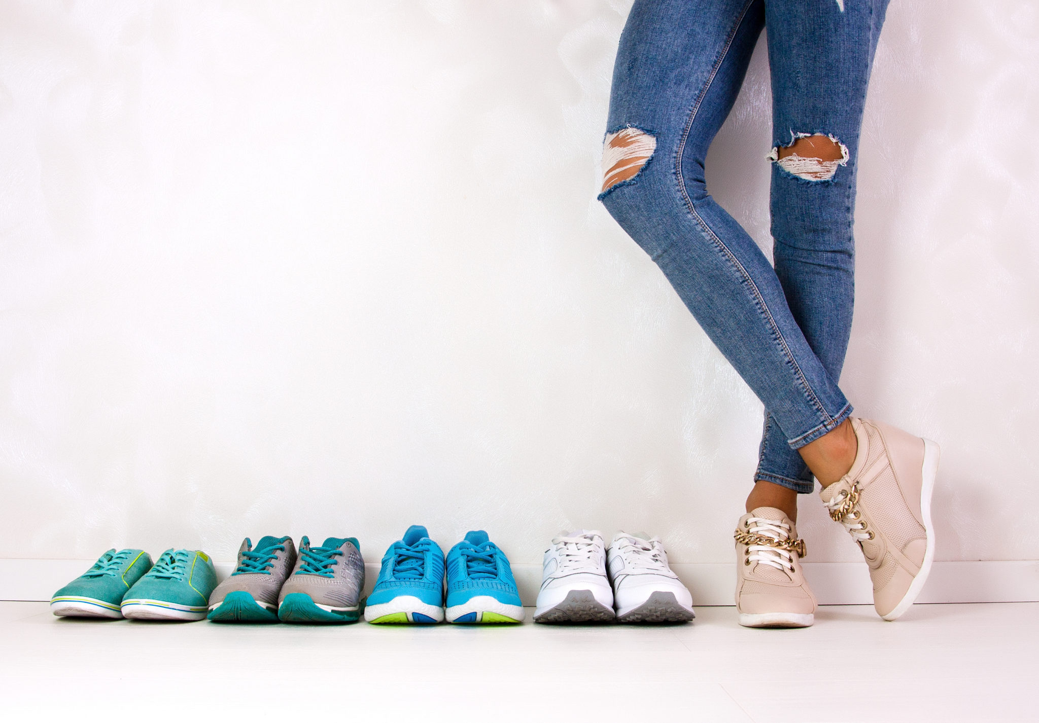 A sporty girl in jeans chooses which sneakers to go for training Several pairs of sports shoes and legs