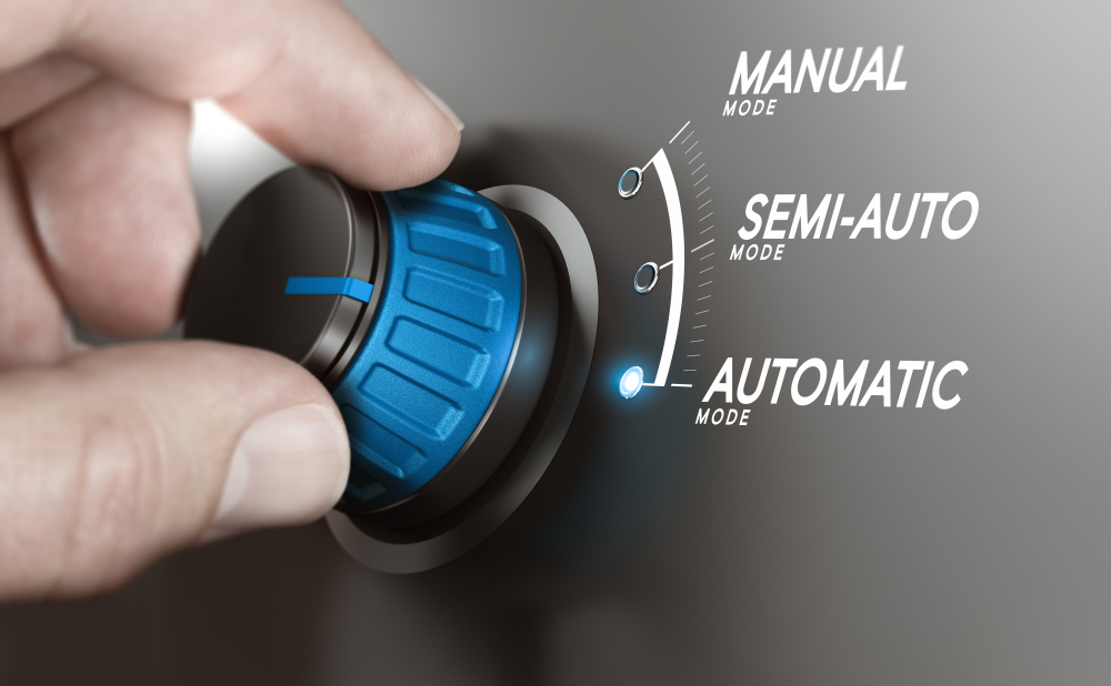 Hand turning a knob over grey background and selecting the automatic mode Manufacturing process automation automatic testing concept